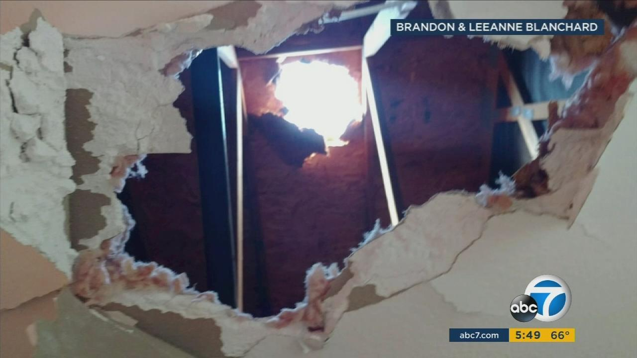 A hole from chunks of ice that may have fallen from an airplane are shown at a Chino home.