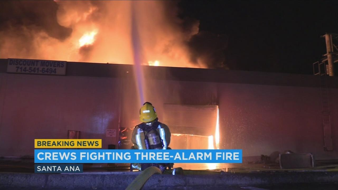 A fire tore through a commercial building Wednesday morning in Santa Ana, but firefighters knocked down the flames before they could spread to a nearby gas station and paint store.