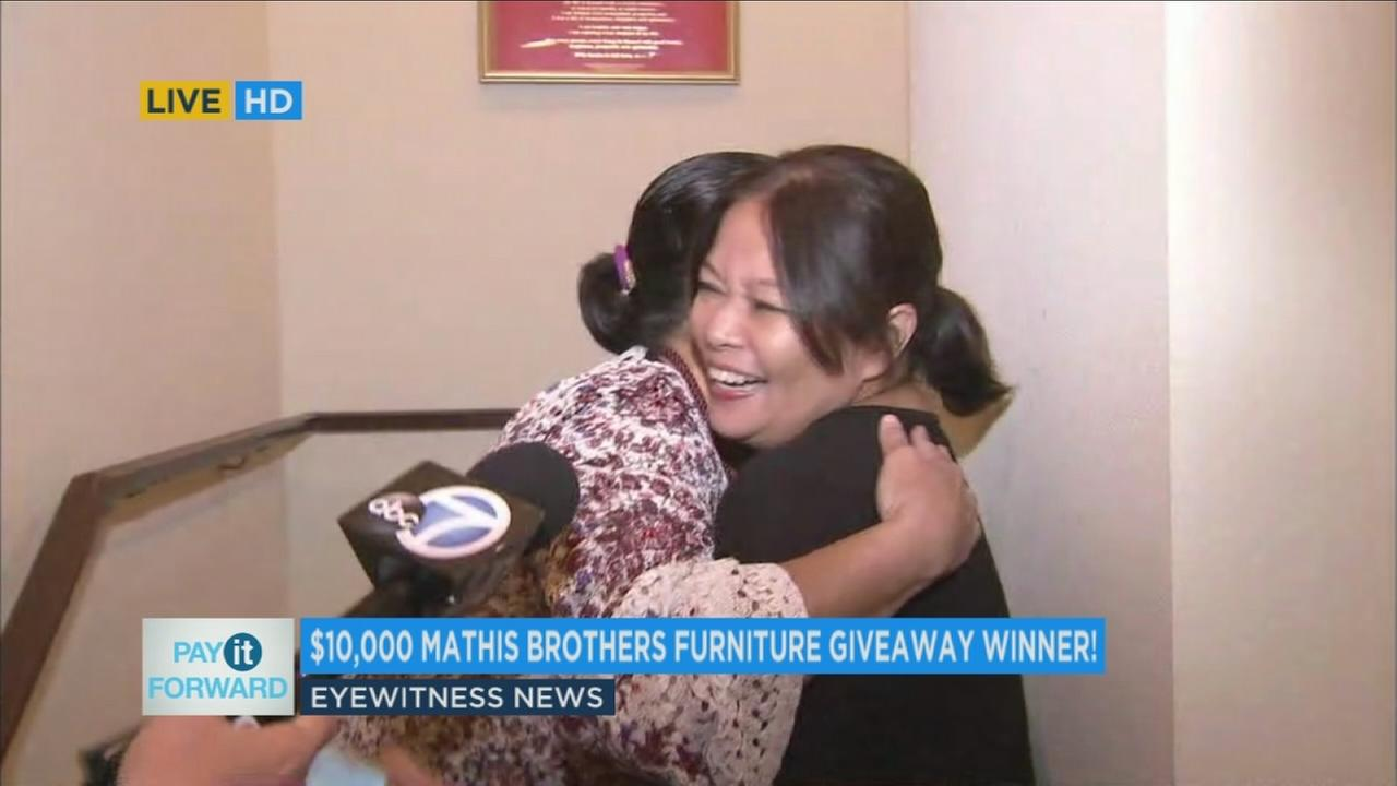The winner of the Mathis Brothers furniture giveaway and a relative hug after learning she had won.