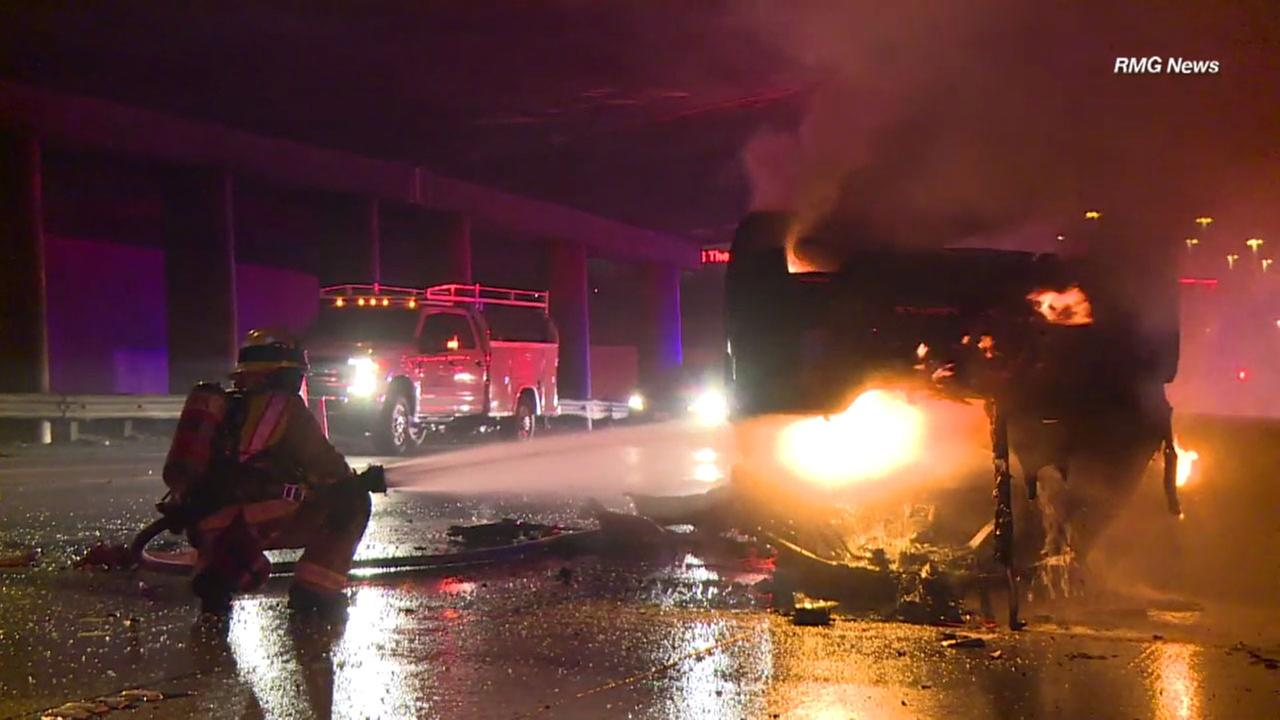 A firefighter worked to put out a blaze that erupted after a driver crashed his vehicle on the 5 Freeway in Burbank on Friday, Nov. 10, 2017.