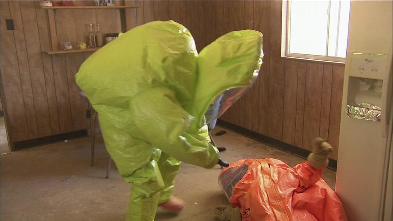 ABC7 reporter Brandi Hitt (in yellow) and DEA Special Agent Jamie Nassour (orange) participate in a simulated response to a fentanyl drug exposure.