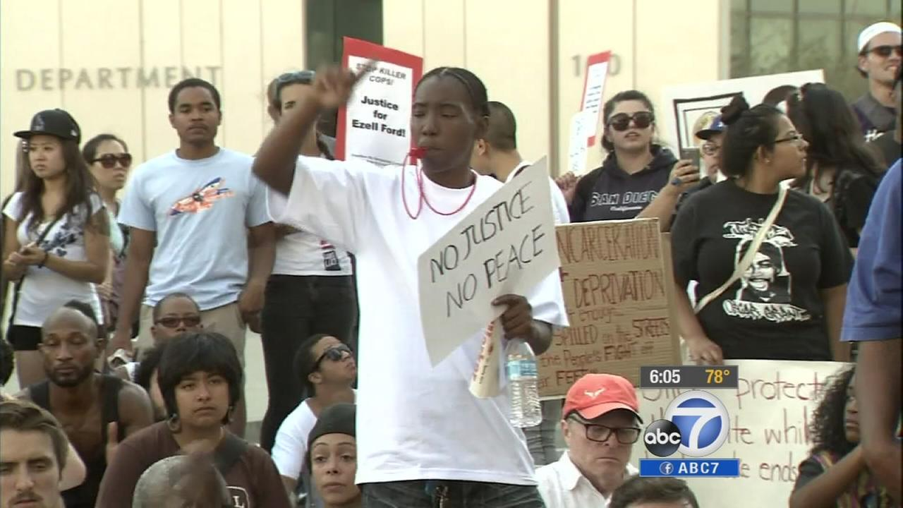 A protester outside the Los Angeles Police Department headquarters holds a sign that says, No justice, no peace on Sunday, Aug. 17, 2014.
