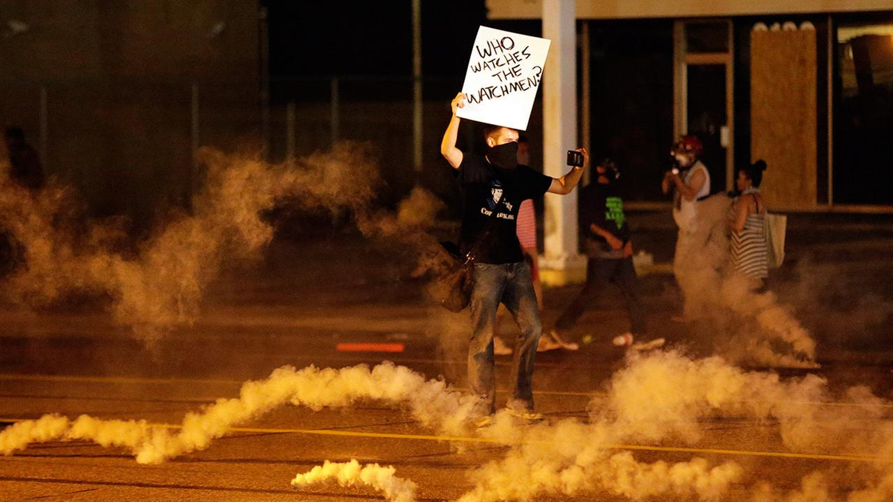 A protester stands in the street after police fired tear gas to disperse a crowd Sunday, Aug. 17, 2014, during a protest for Michael Brown.