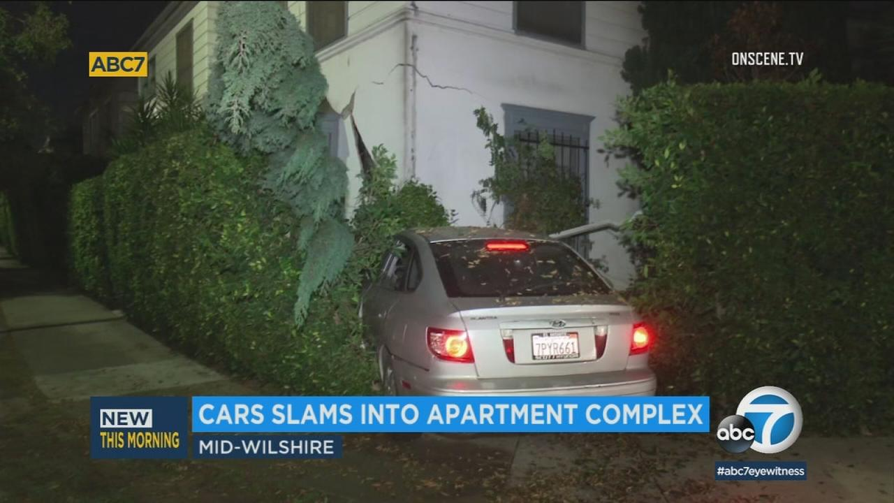 A driver was hospitalized and eight people were displaced from their homes after a car slammed into an apartment complex Sunday, Dec. 3, 2017, in the Mid-Wilshire District of L.A.