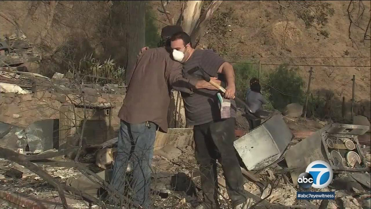 Two mean are seen embracing each other on Saturday, Dec. 9, 2017, as they pick up whats left of Kagel Canyon homes after the Creek Fire.