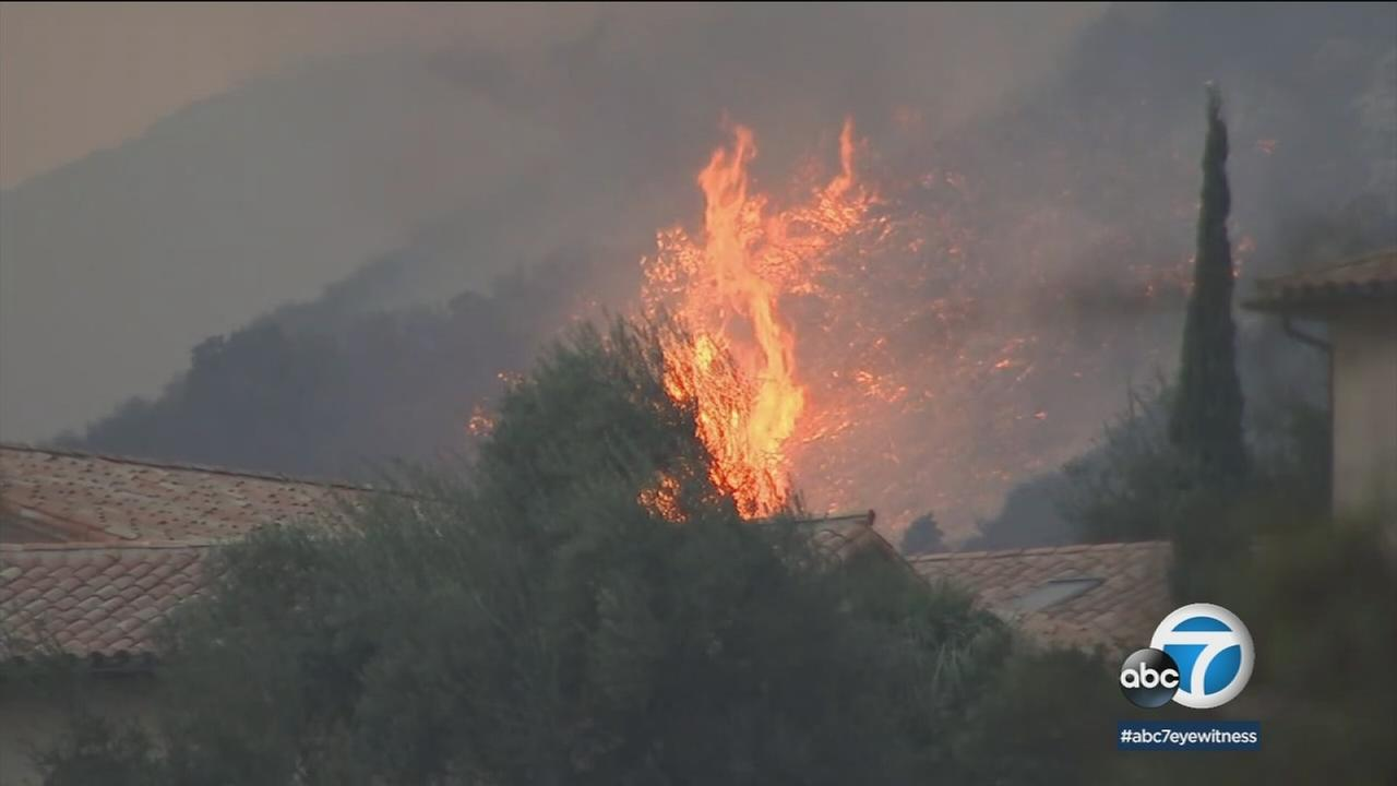 A flare up behind a home in the path of the destructive Thomas Fire is shown in Montecito.