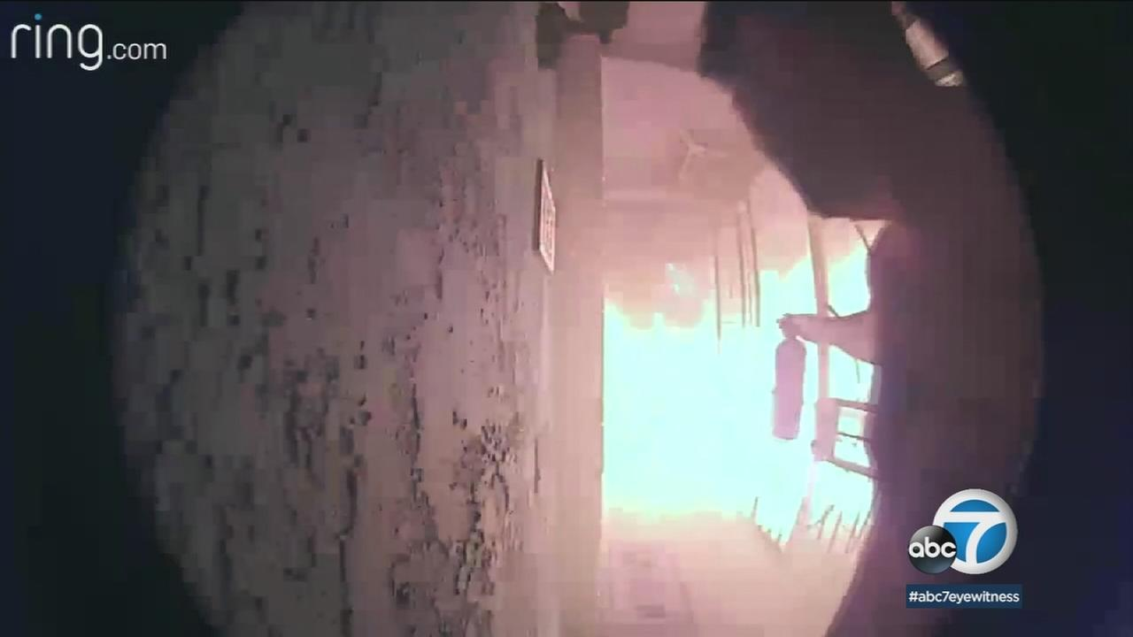 Video shows a Corona homeowner trying to extinguish a blaze outside his home after his doorbell alerted him on Sunday, Dec. 17, 2017.