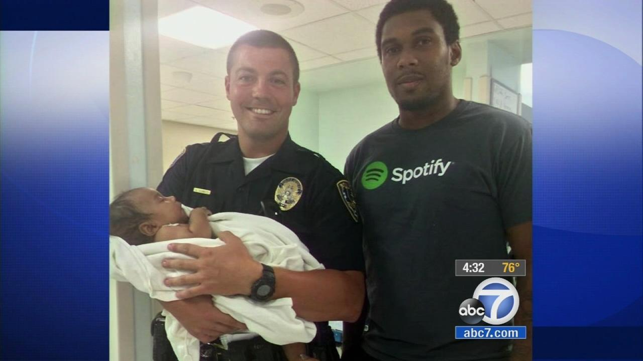 Riverside Police Officer Victor Schmitz poses with Kahlid Williams and his son Alexander.