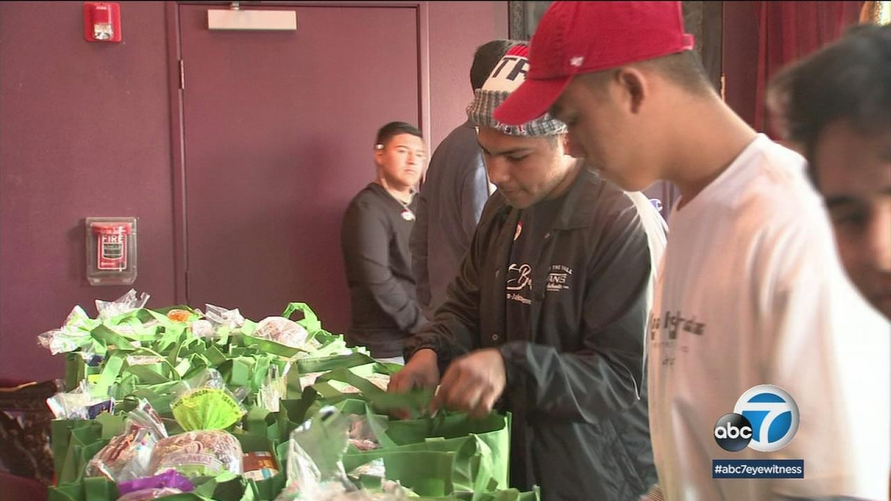 Marcus Guillen, 18, is shown stuffing bags with goodies during a volunteer event for his high schools Leos club.