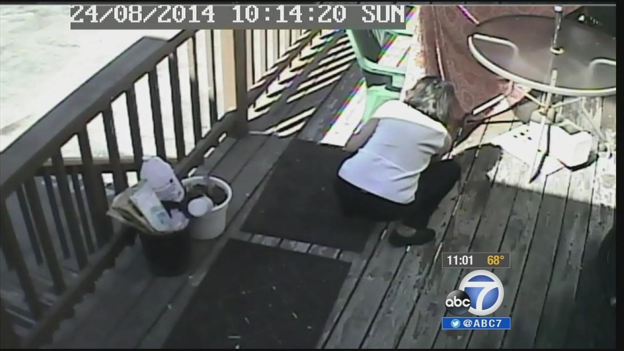 A woman smokes a cigarette then bends down to set patio furniture on fire in El Segundo.