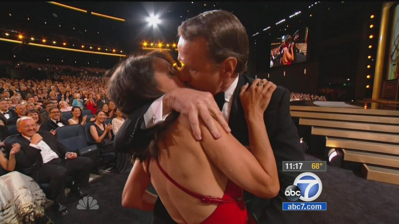 Julia Louis-Dreyfus and Bryan Cranston kiss at the 2014 Emmy Awards.