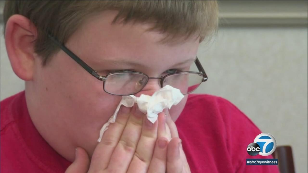 In a file photo, a boy is seen blowing his nose during the flu season.