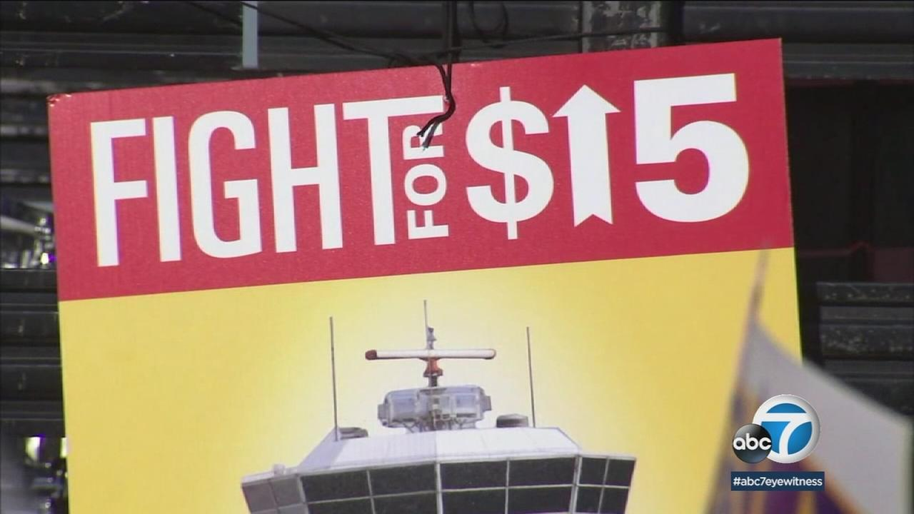 A sign saying Fight for $15 is shown in a photo.