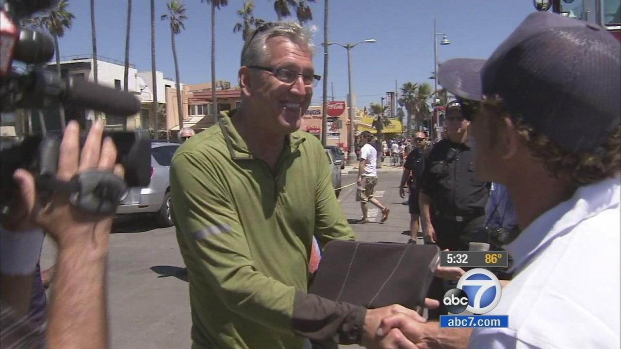 Bob Kilroy, who survived a lightning strike at Venice Beach, shakes hands.