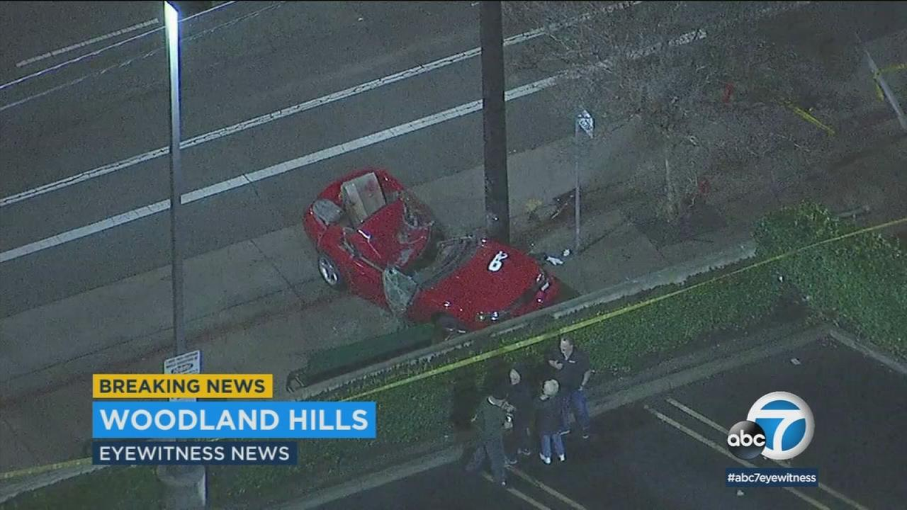 A red sports car is seen mangled after striking a utility pole in Woodland Hills on Monday, Jan. 8, 2018.
