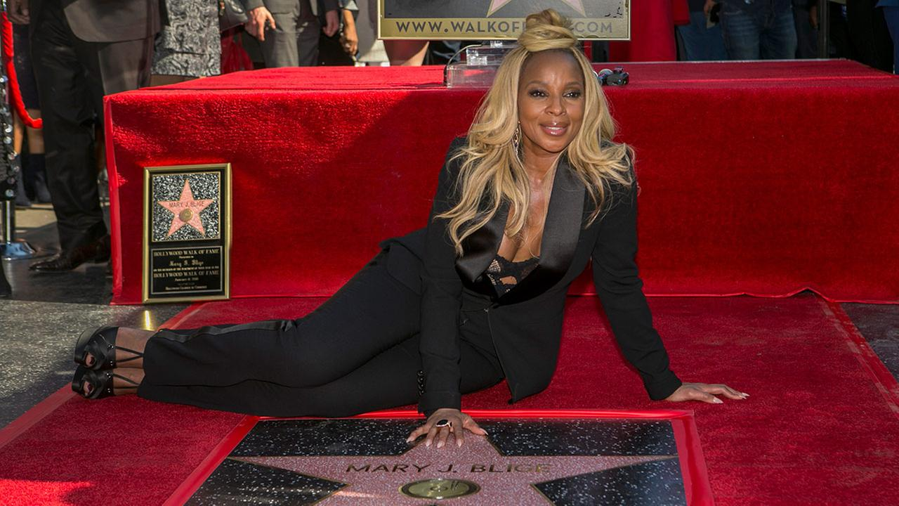 Actress and R&B singer Mary J. Blige touches her star at a ceremony honoring her on the Hollywood Walk of Fame in Los Angeles, Thursday, Jan. 11, 2018.