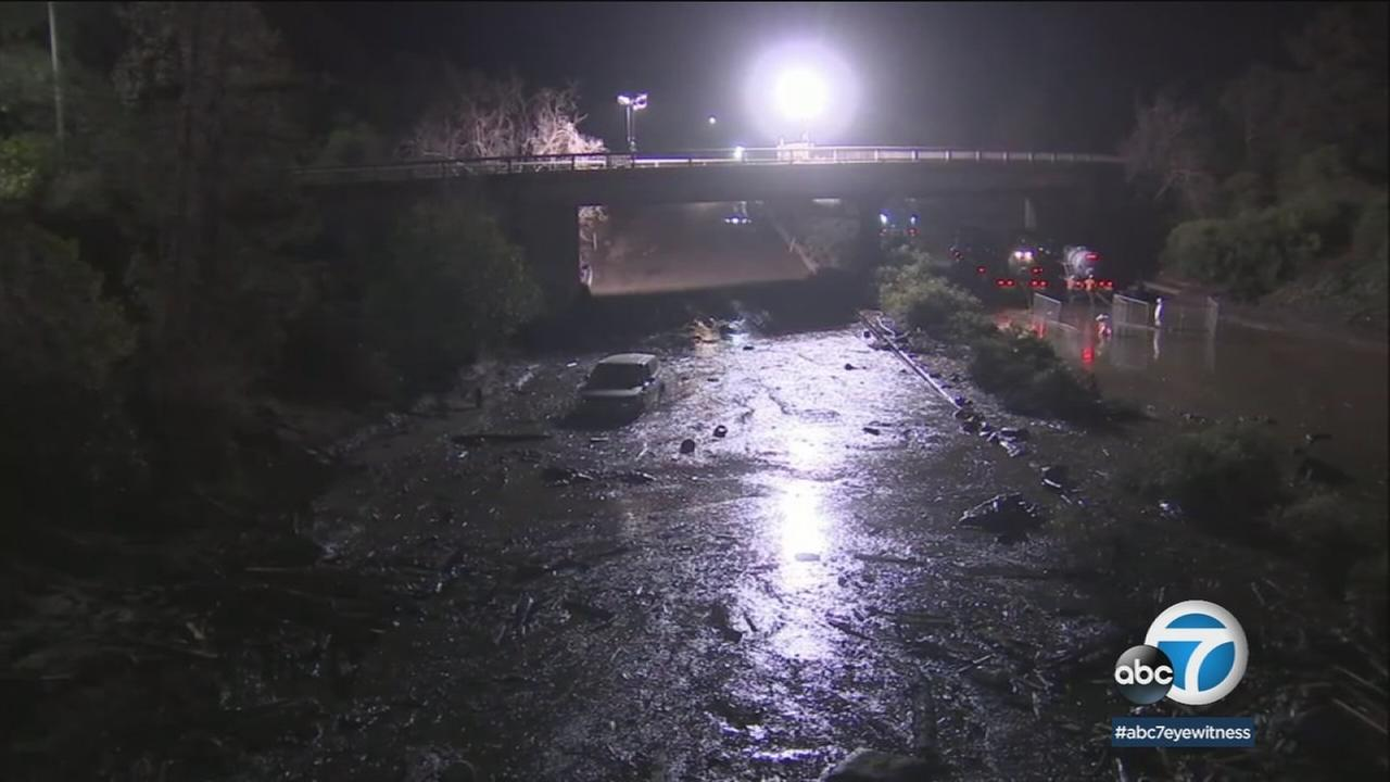 A spotlight shines on the mud, water and debris clogging the 101 Freeway in Montecito as crews work late into the night to clean it up on Saturday, Jan. 13, 2018.