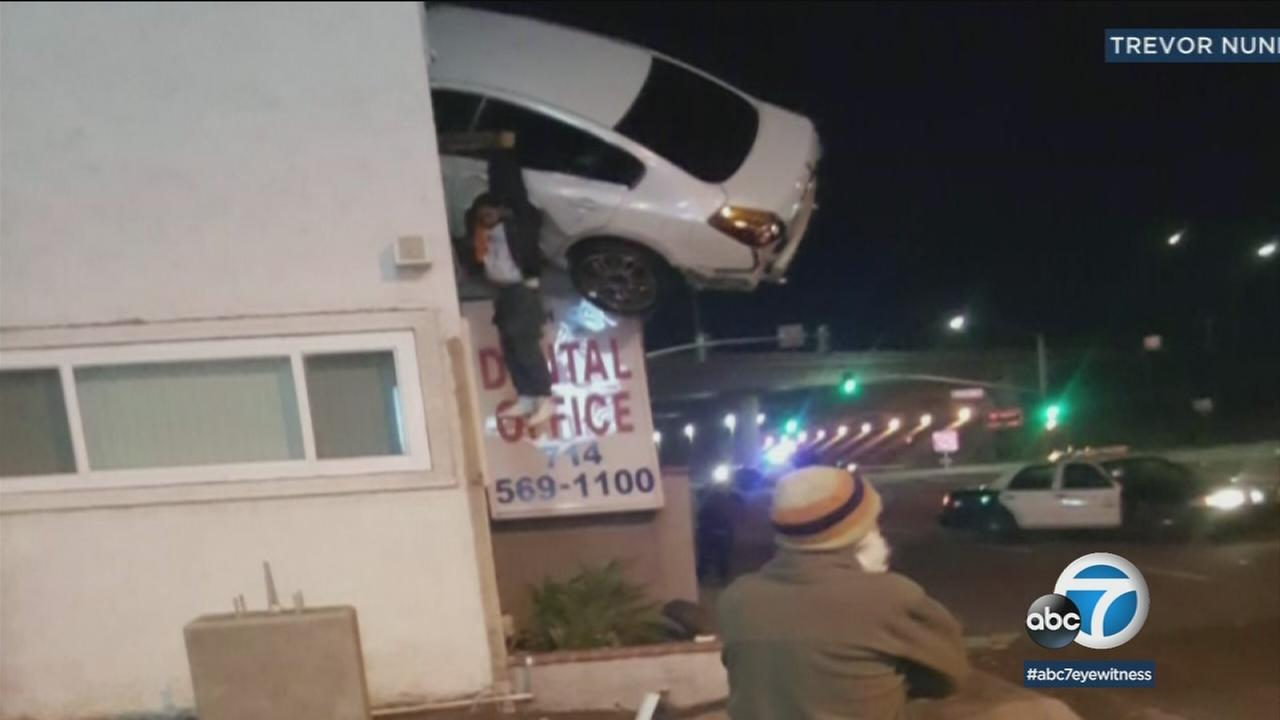 A driver was dangling from the side of a car after a crash launched his vehicle into the second story of a Santa Ana building.