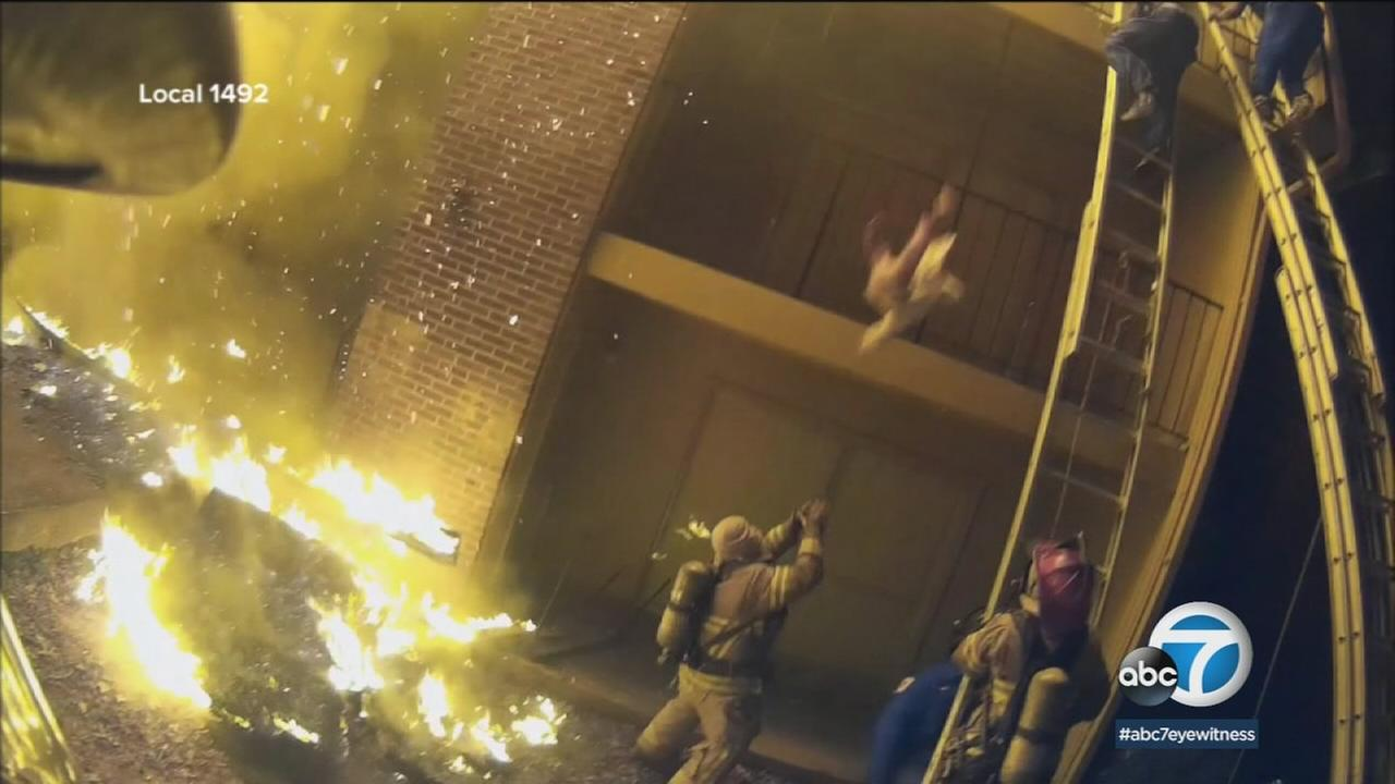 Incredible video of a fire rescue near Atlanta shows a firefighter catching a child thrown from a burning apartment three floors up.