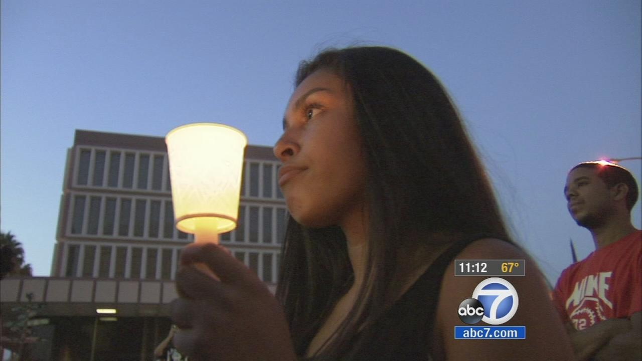 A woman holds a candle during a vigil held for the victims of violence in San Bernardino on Thursday, Sept. 4, 2014.