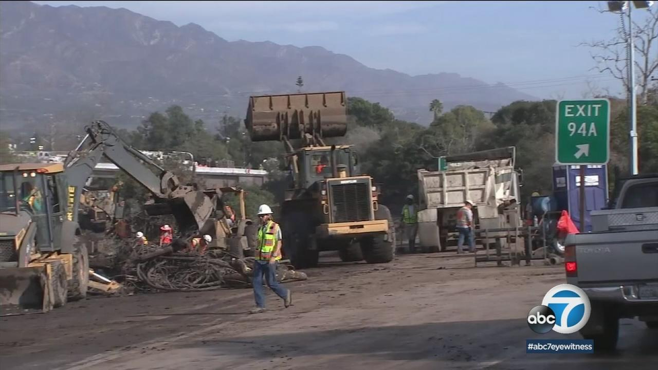 Crews work on clearing out the 101 Freeway in Montecito of muck and mud blocking the roadway.