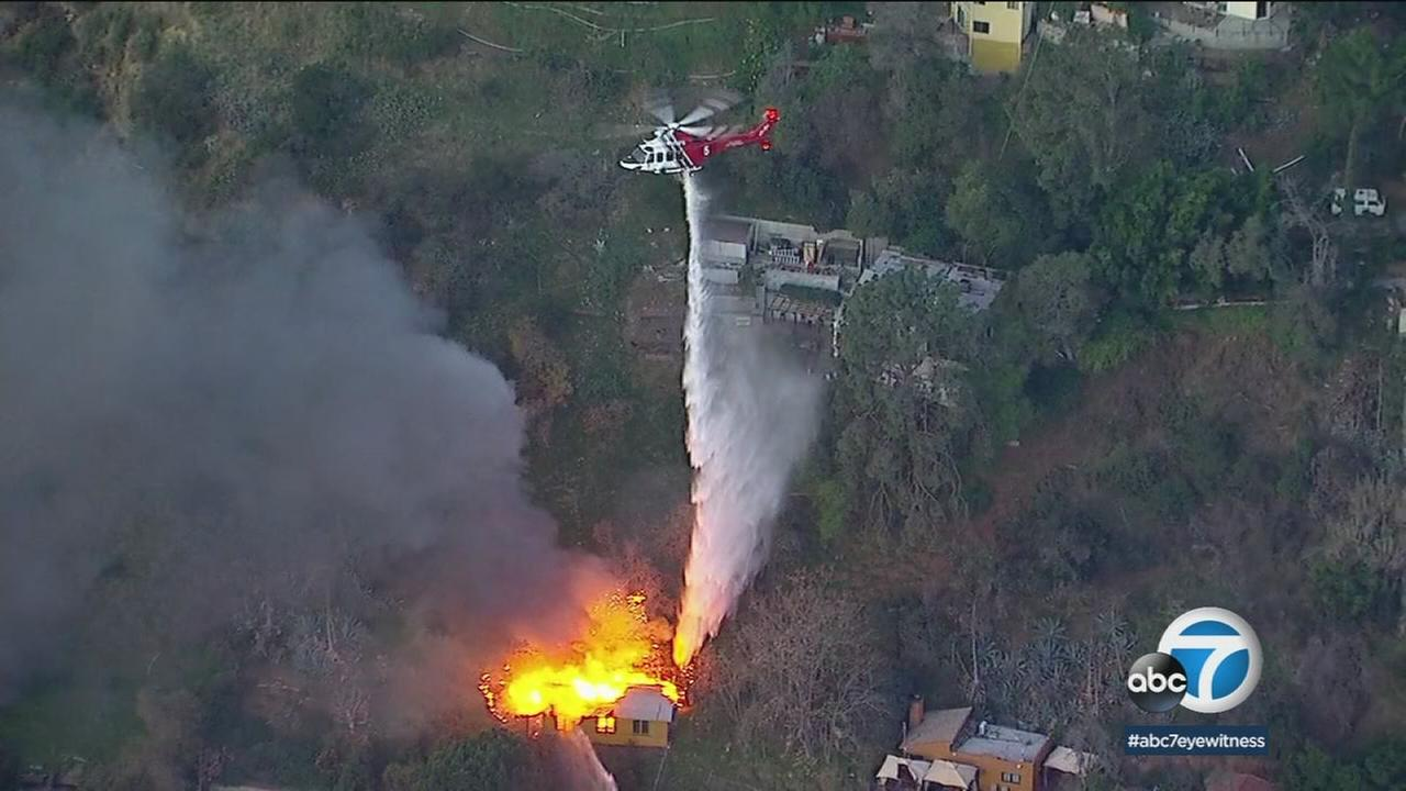 A helicopter drops water on a burning structure in the Hollywood Hills area on Friday, Jan. 26, 2018.