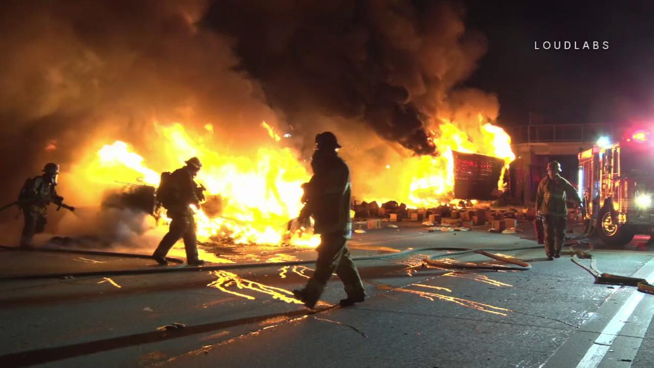 Firefighters work to extinguish a fire after a semi-truck crashed into an overpass pillar on the 5 Freeway in Sun Valley on Friday, Jan. 26, 2018.