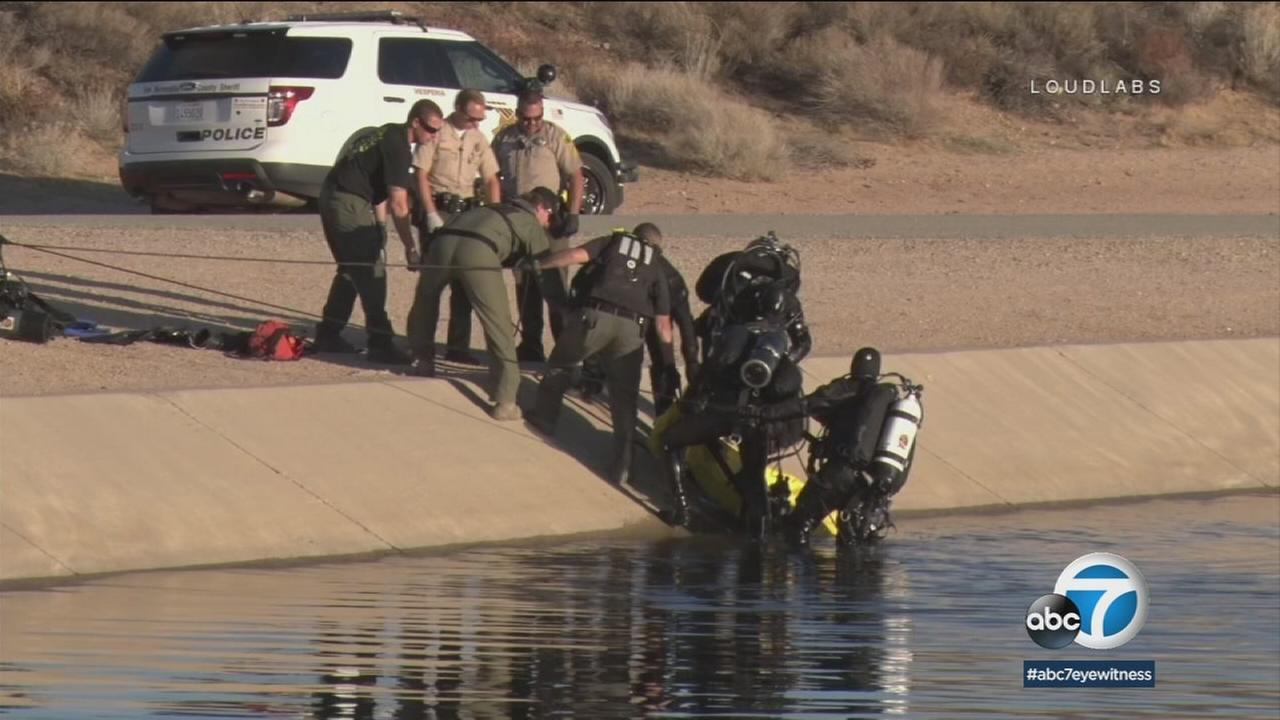 Dive teams pull out the body of a father who died while rescuing his son from the California Aqueduct in Hesperia on Sunday, Feb. 4, 2018.