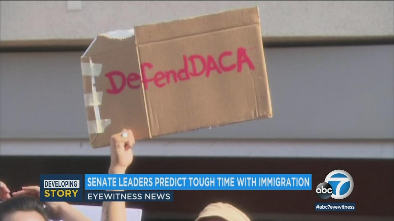 A sign reads, Defend DACA, the Deferred Action for Childhood Arrivals program.