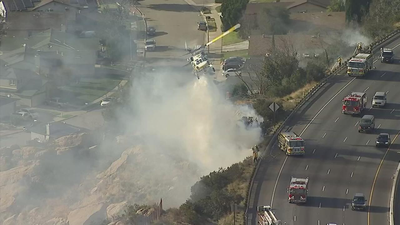 An aerial unit douses the flames that broke out along the 118 Freeway in Simi Valley Monday.