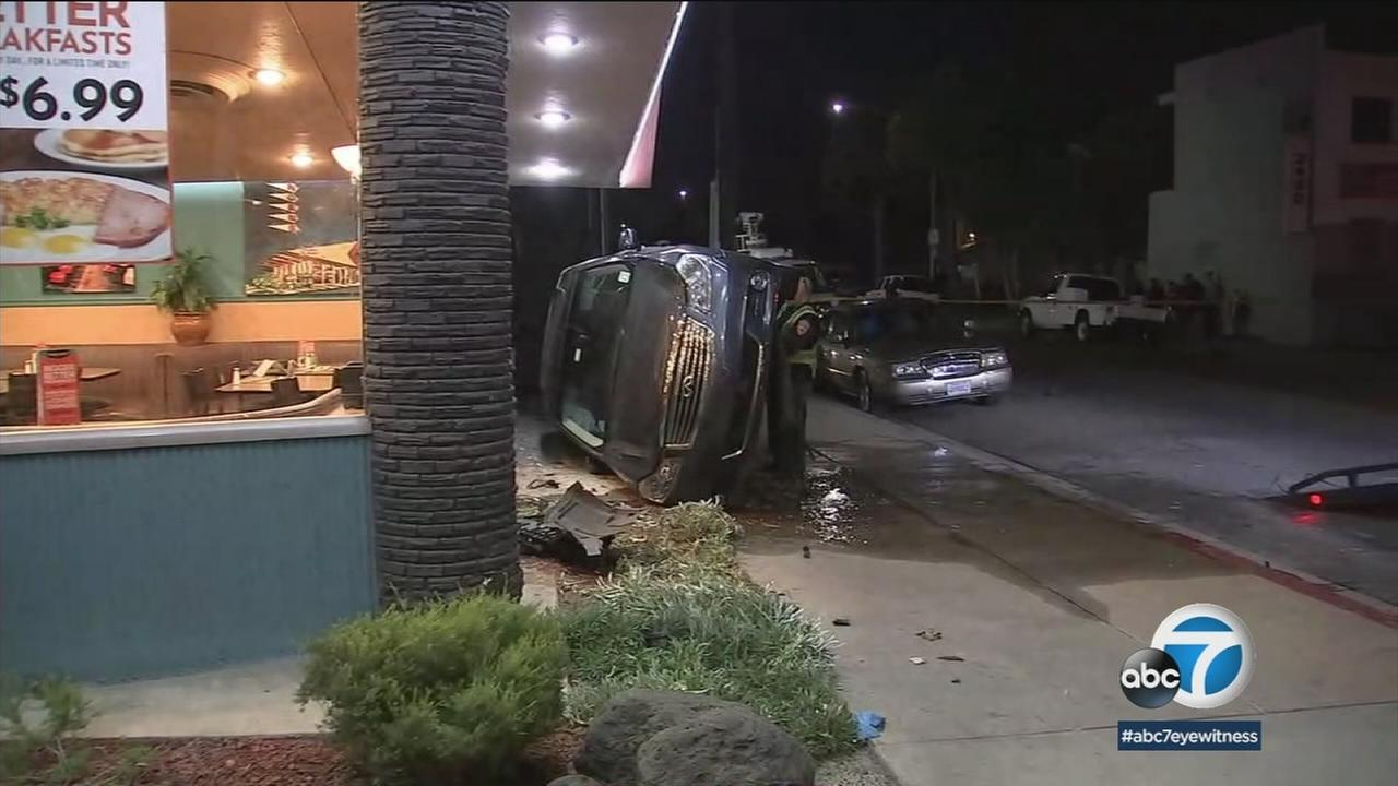 A car on its side is shown in front of a Norms restaurant in Huntington Park after a chase.