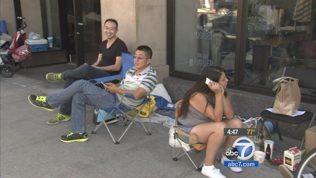 A group of people wait outside an Apple store in anticipation of the iPhone 6 release on Thursday, Sept. 18, 2014.