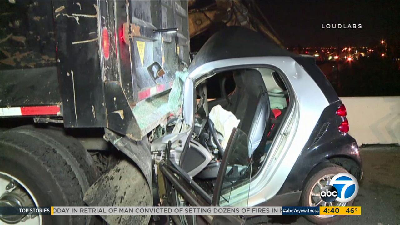 Stunning video shows a Smart Car that was crushed after slamming into the back of a dump truck on the 405 early Monday, March 5, 2018.