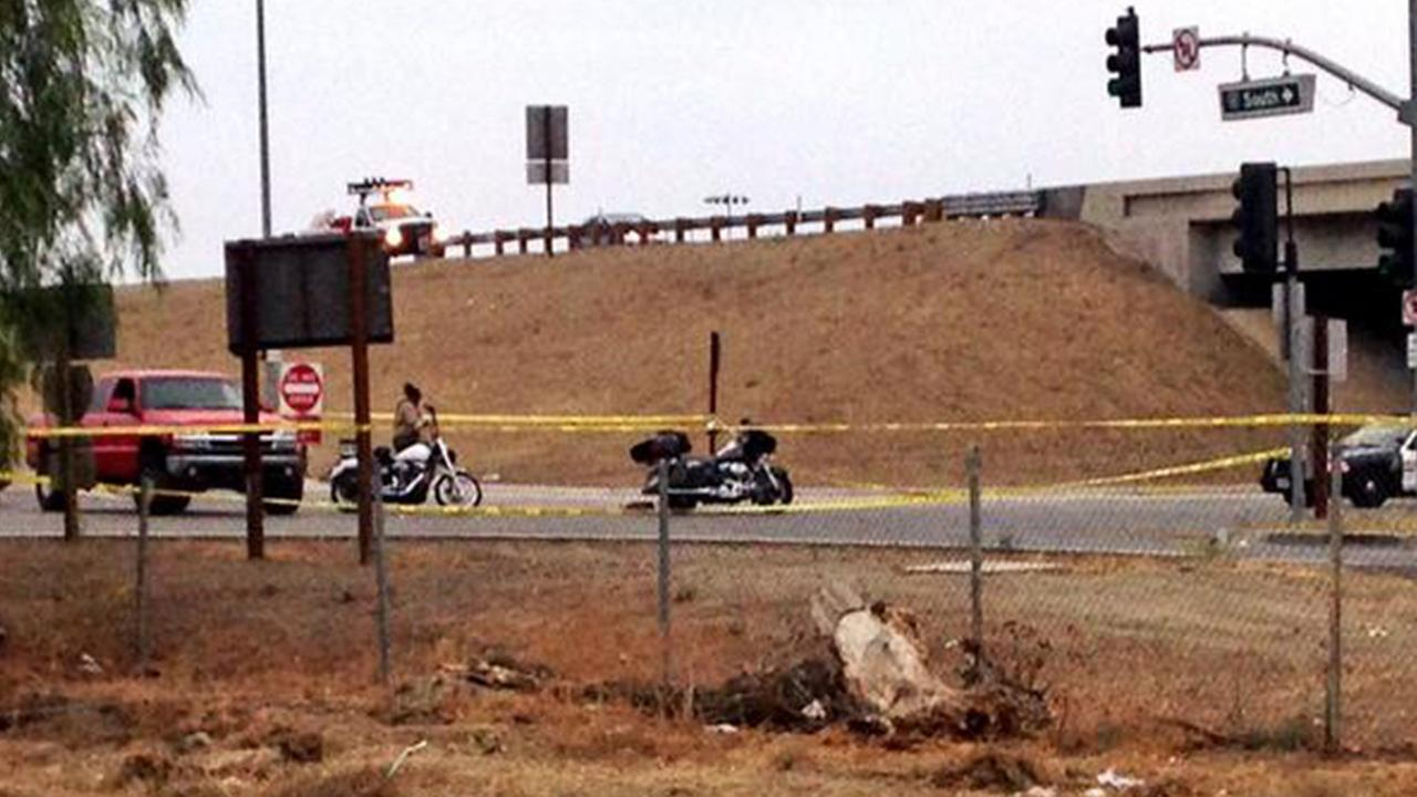 Authorities investigate a motorcycle shooting on the 15 Freeway near Corona on Sunday, Sept. 21, 2014.