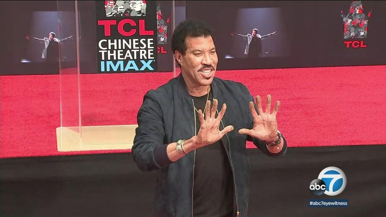 Lionel Richie shows off his hands after dipping them in cement at TCL Chinese Theatre in Hollywood Wednesday, March 7, 2018.