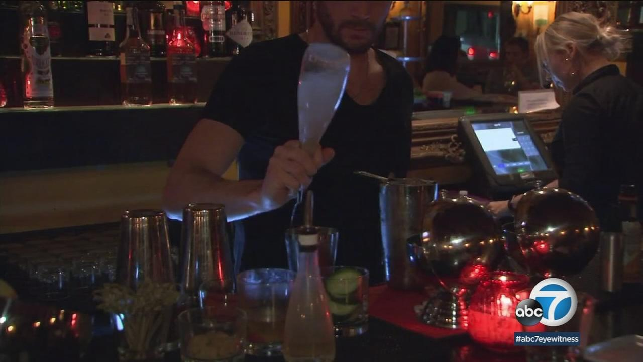 A SoCal bartender seen pouring a drink at a bar in an undated photo.