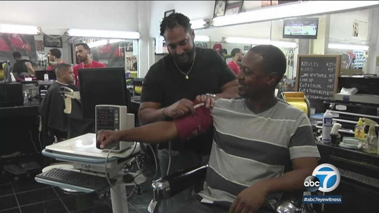 Barber Eric Muhammad takes client Marc Sims blood pressure Monday, March 12, 2018.