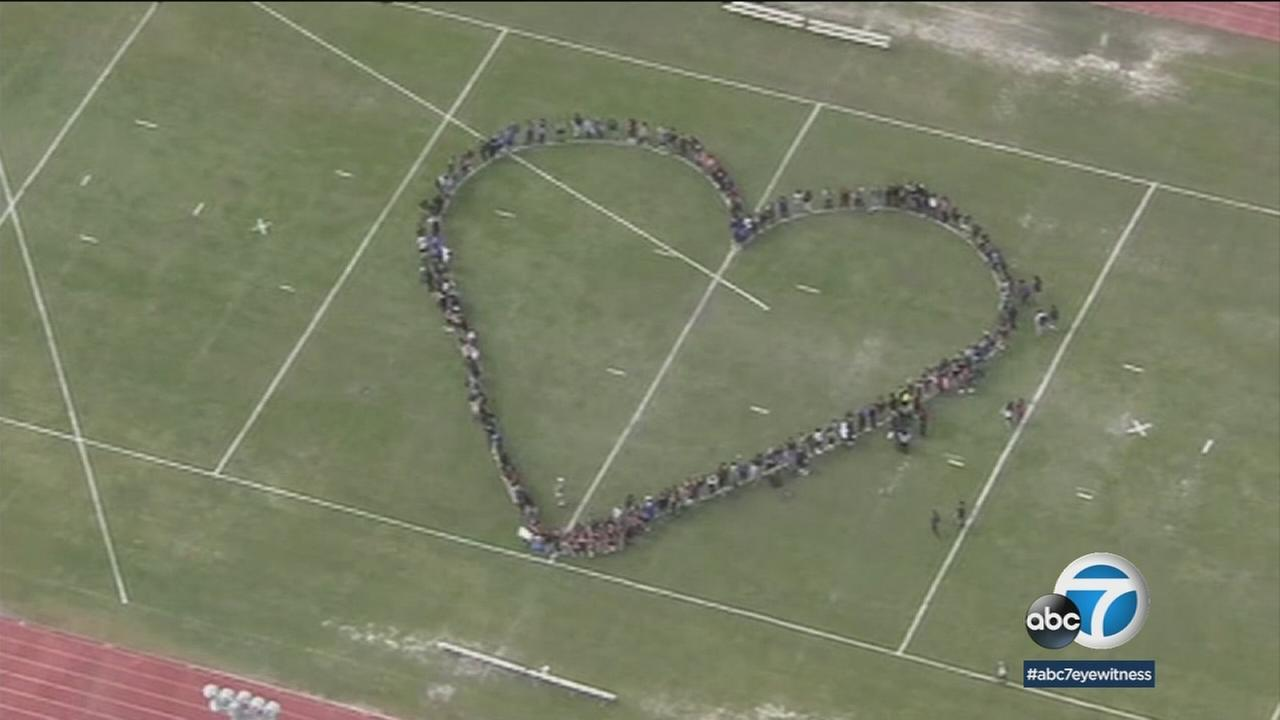 Students form a heart in a protest picture on a football field.