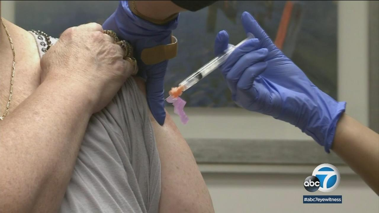 A doctor gives an older woman the new shingles vaccine.