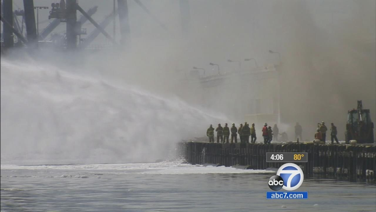 The dock at the Port of Los Angeles was still smoldering Tuesday afternoon after a stubborn fire burned all night, Sept. 23, 2014.