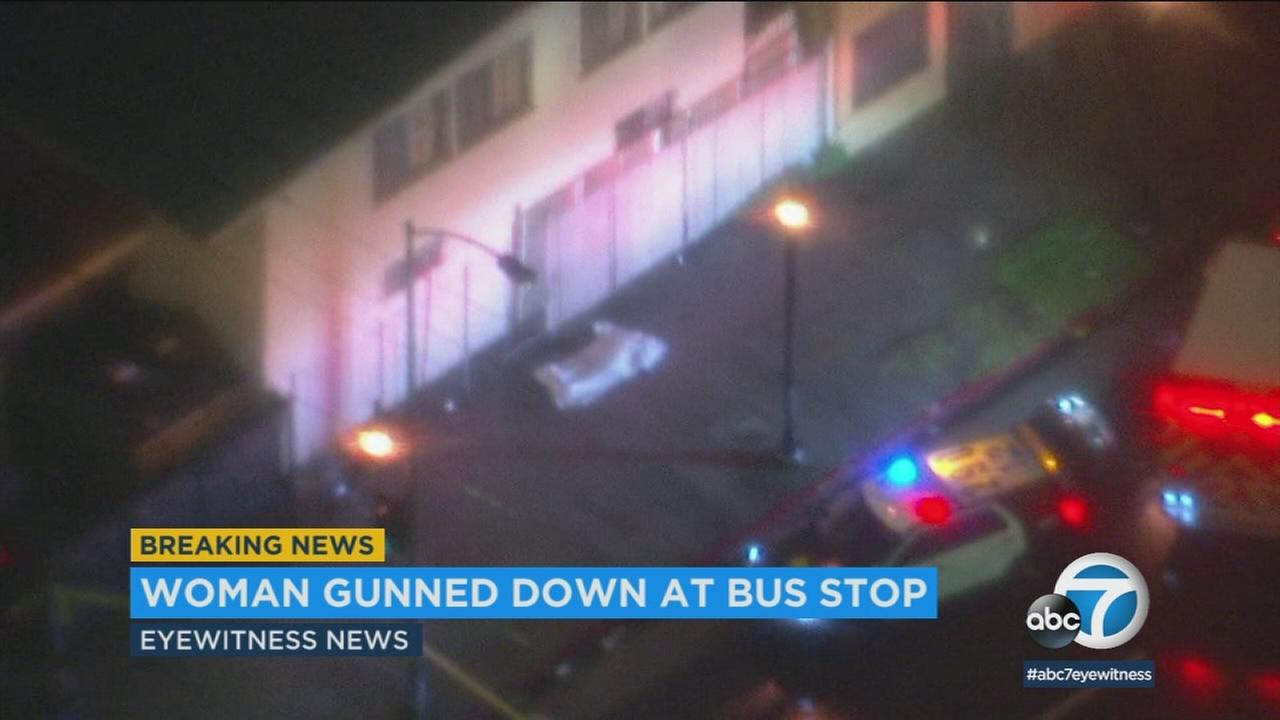 Footage from AIR7 HD shows a body covered in a sheet at a South Los Angeles bus stop after reports of a woman being shot in the area on Friday, March 16, 2018.