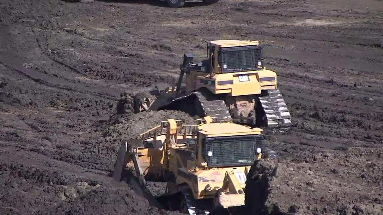 Bulldozers moved dirt and shifted it around near catch basins in Los Angeles County to keep burn areas from being inundated with mud and debris from an incoming rainstorm.