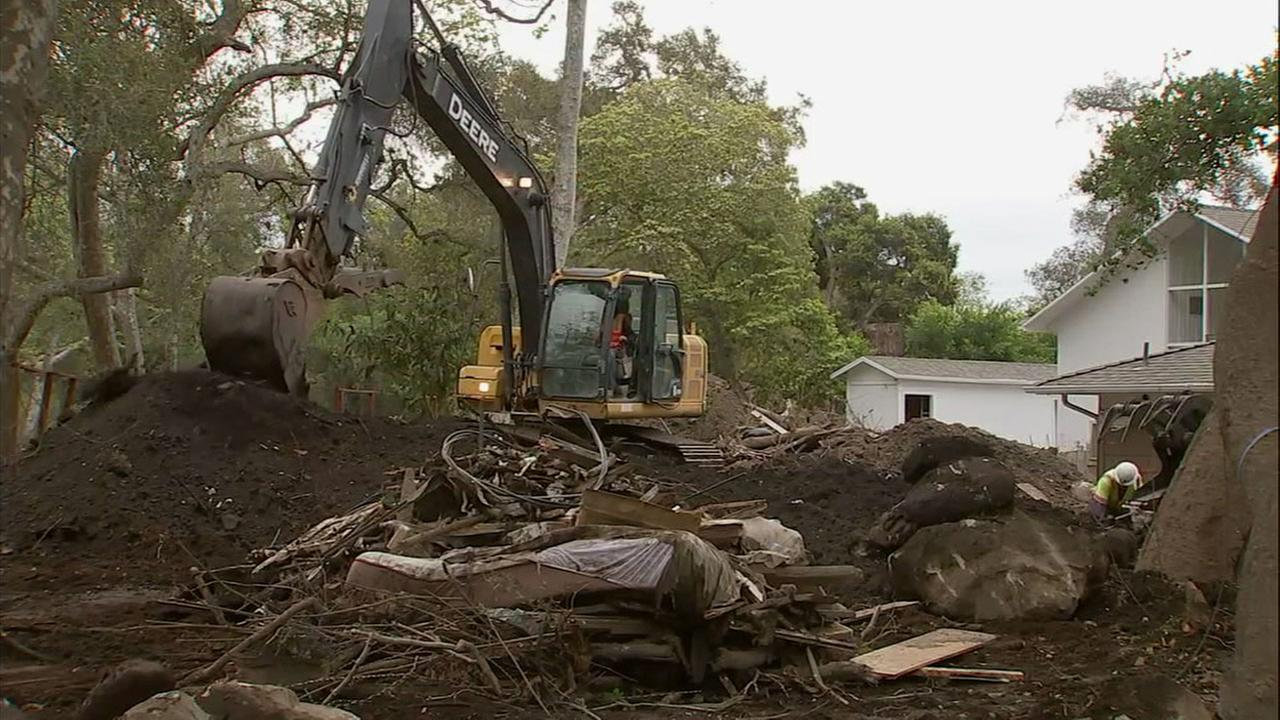 An excavator is shown moving around sediment and dirt to clear out basins in Montecito ahead of a major rainstorm headed for the Southland.