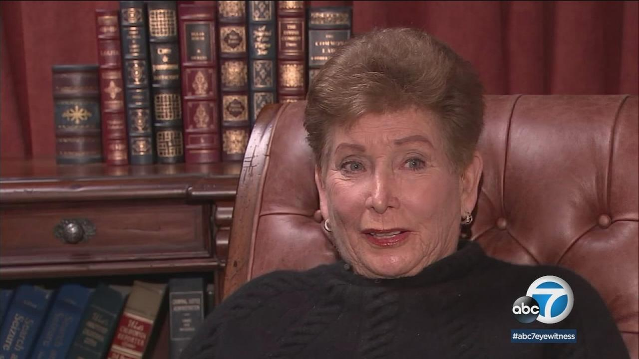 Tennis umpire Lois Goodman is suing the Los Angeles County coroner for falsely accusing her of murdering her husband.