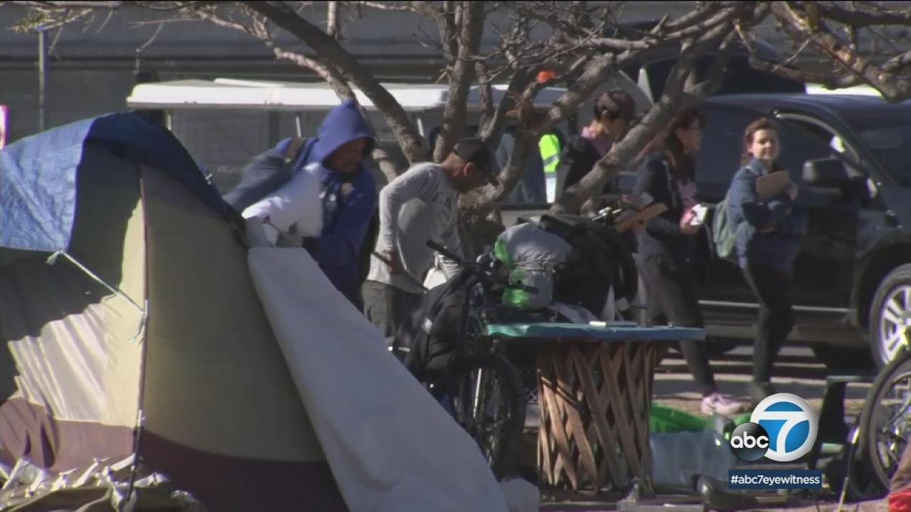 Homeless residents are shown at a camp along the riverbed in Santa Ana before it was removed.