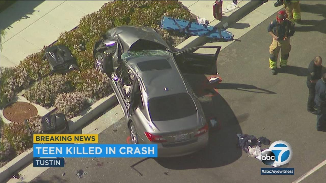 A mangled 2011 Infiniti sedan is shown along a street in Tustin after it rolled over, resulting in the death of a teenage boy on Friday, March 23, 2018.