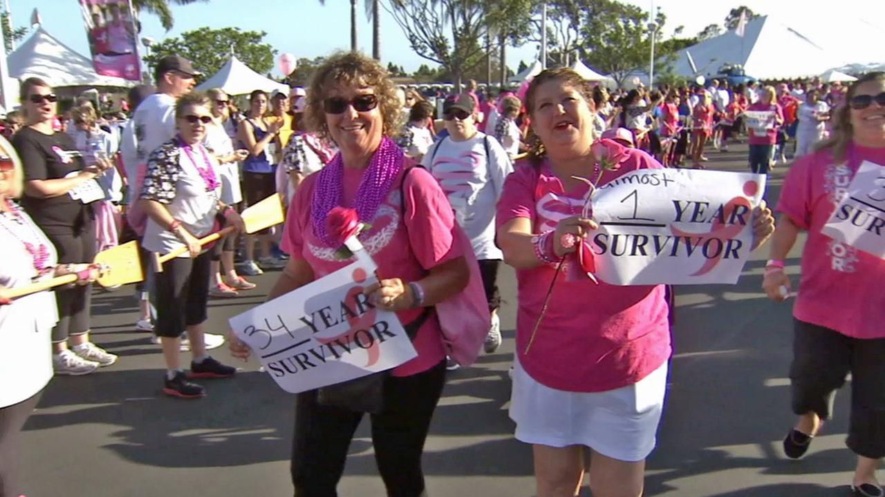 Two breast cancer survivors hold up signs at the Orange County Race for the Cure in Newport Beach on Sunday, Sept. 28, 2014.