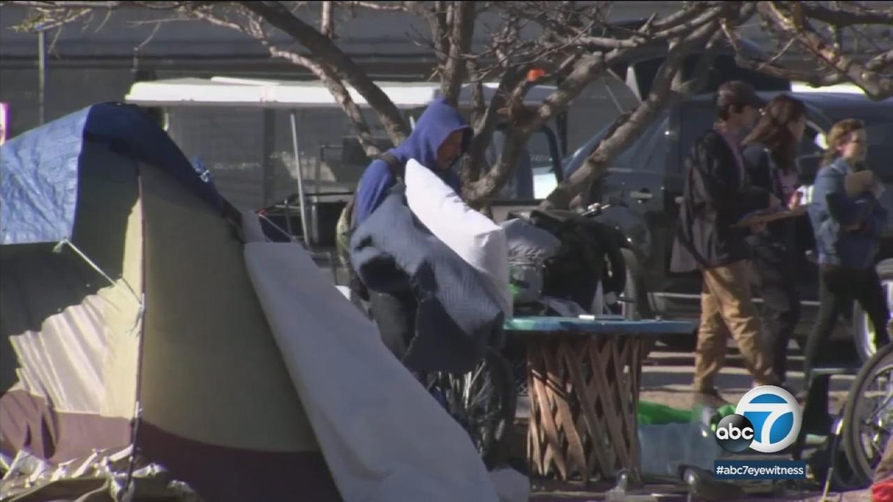 A homeless encampment is shown in stock footage.