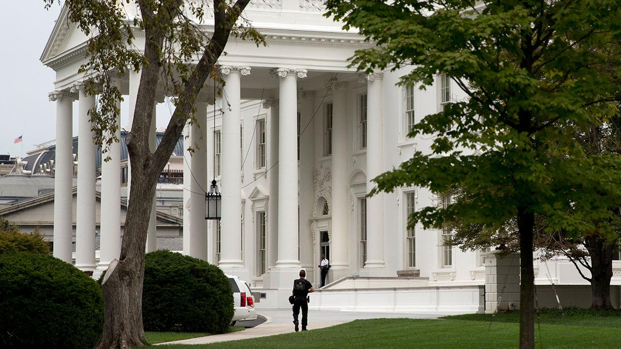 A security member of the Secret Service approaches the North Portico of the White House in Washington Monday, Sept. 29, 2014.