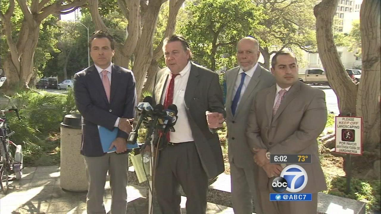 Attorneys for the plaintiffs suing Los Angeles Unified School District stand behind a podium during a news conference Monday, Sept. 29, 2014.